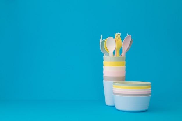 プラスチックパステル食器青い背景コピースペース