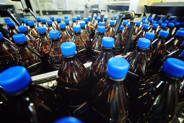 공장 배경의 컨베이어 벨트에 맥주 또는 달콤한 음료와 함께 파란색 뚜껑이 달린 노란색 플라스틱으로 만든 플라스틱 pet 병. 음료의 산업 식품 생산.