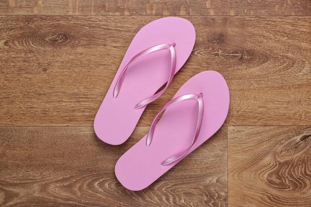 Plastic pink flip flops on the floor. top view