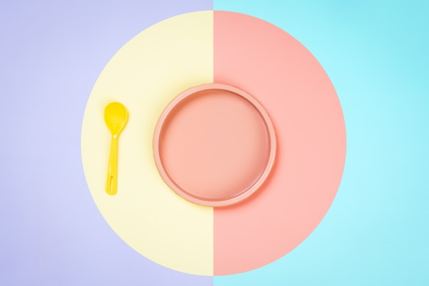 Plastic pink plate, blue and a yellow spoon in a yellow-pink isolated background.