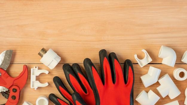 広告スペースと木製の背景にプラスチックパイプ切削工具と手袋。