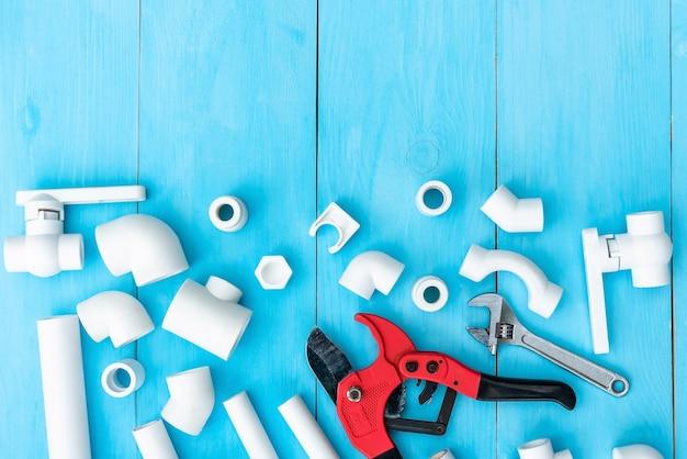Пластиковые трубы для водопровода, инструменты для резки труб, гаечный ключ, уголки, держатели, краны и переходники и на голубом фоне. скопируйте пространство. вид сверху.