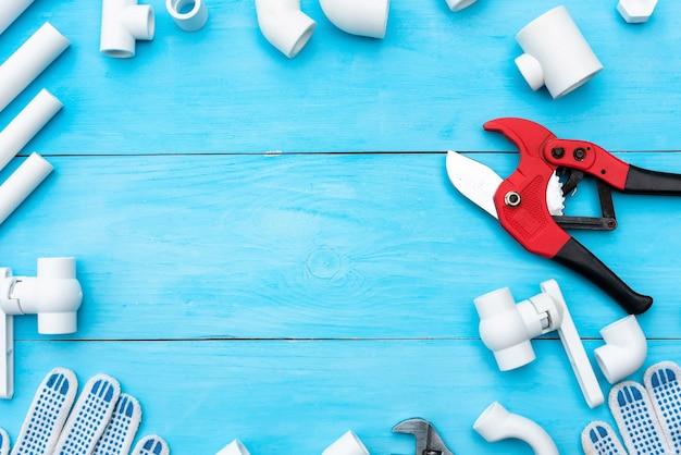 水系用のプラスチックパイプ、パイプ切削工具、レンチ、コーナー、ホルダー、蛇口、アダプター、水色の背景の作業用手袋。