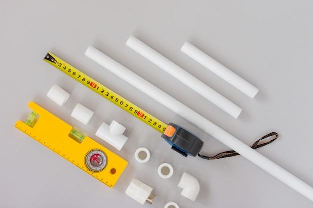 수도 시스템용 플라스틱 파이프, 눈금자 및 회색 배경의 측정 레벨. 수리 서비스, 판매, 온라인. 플랫 레이. 공간을 복사합니다.