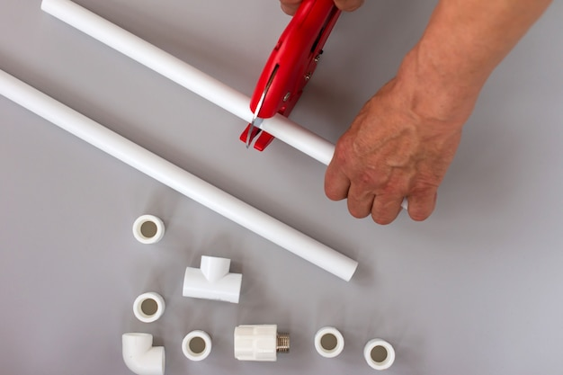 Plastic pipes for the water system on grey background. repair service, sale, online. flat lay. copy space.