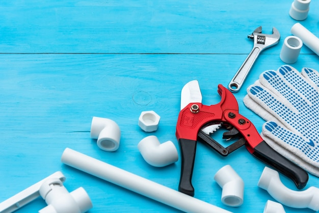 Plastic pipes for the water system, pipe cutting tools, wrench, corners, holders, taps and adapters and work gloves on a light blue background. copy space.