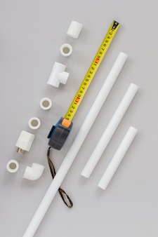 Plastic pipes for the water system, ruler and measuring level on grey background. repair service, sale, online. flat lay. copy space.
