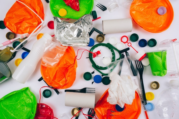 Plastic pollution concept. be plastic free. broken single-use colorful plastic items on white background.
