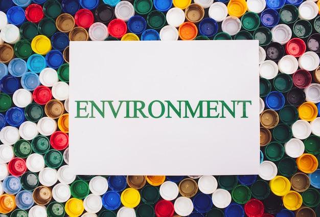 플라스틱 오염 개념. 플라스틱이 없어야합니다. 다른 플라스틱 뚜껑, 평면도의 배경색에 환경 단어로 종이. 일회용 플라스틱, 환경을 돕기위한 eu 유럽 지침