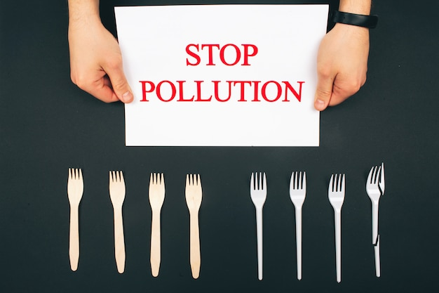 プラスチック汚染の概念。プラスチックフリー。手は、環境にやさしいゼロの廃棄物と使い捨てフォークの近くに「汚染を止める」という言葉の入った紙を持っています。暗い背景、上面図でフォークが並んでいます。