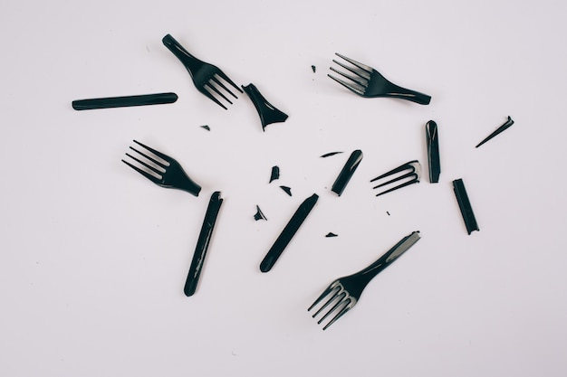 Plastic pollution concept. plastic free. scattered broken single-use black forks