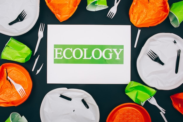 プラスチック汚染は海洋生態を破壊します。暗い背景に使い捨ての壊れたプラスチックプレートとフォークの中心にある「エコロジー」という言葉の紙。使い捨てプラスチック-環境問題、eu