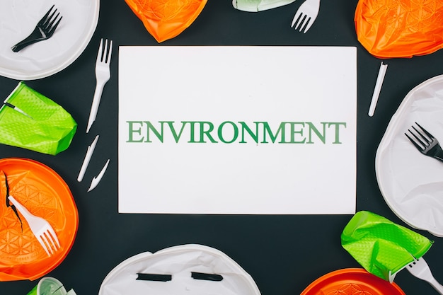 Plastic pollution and environment protection. paper with word environment in the centre of disposable colorful broken plastic plates and forks on dark surface.