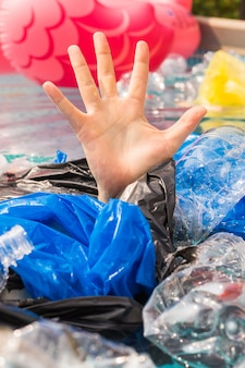 Plastic pollution and environmental problem, man's hand in plastic sea