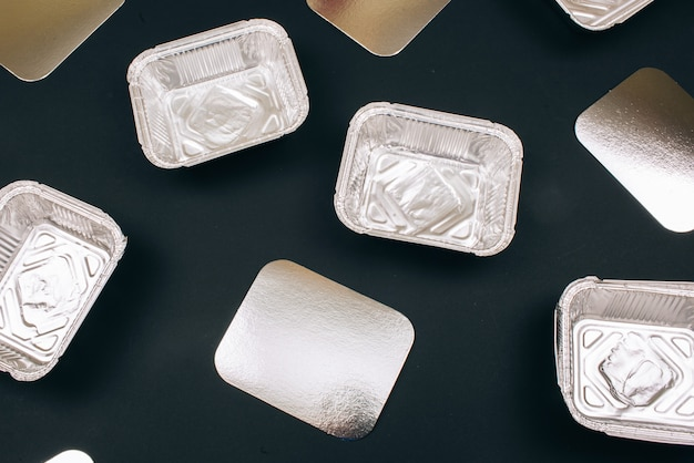 Plastic pollution. foil containers for food and silver cardboards,top view. single-use plastic. an evironmental problem, eu directive