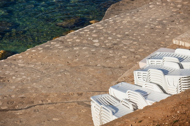 Пластиковые стулья у бассейна в куче у моря