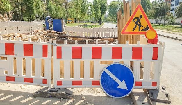 プラスチック製の保護バリアが道路工事の現場を囲います。通りの修理現場近くの赤と白のプラスチック柵。路上工事、道路補修、柵柵。
