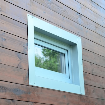 Plastic pvc window in new modern passive wooden house facade wall
