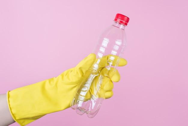 Концепция переработки пластика. обрезанное изображение руки в желтой перчатке, держащей пустую бутылку, изолированную на заднем плане, крупным планом