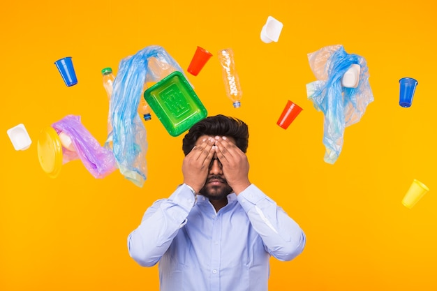Plastic recycling problem, ecology and environmental disaster concept - indian man closed his eyes with hands on yellow wall. he is terrified by trash problems.