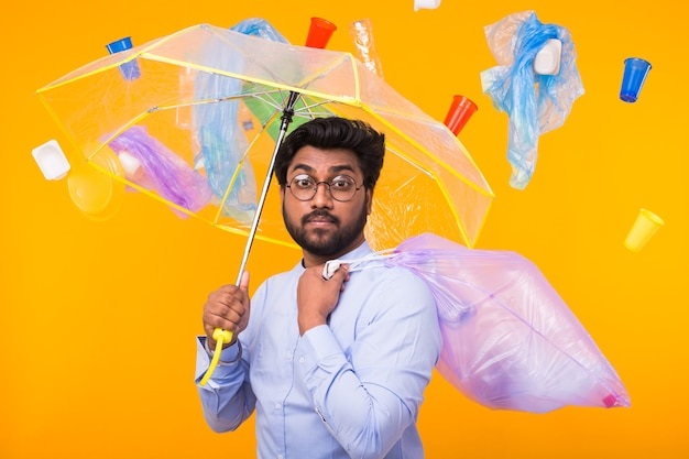 Plastic recycling problem, ecology and environmental disaster concept - indian man hiding from garbage under an umbrella on yellow wall