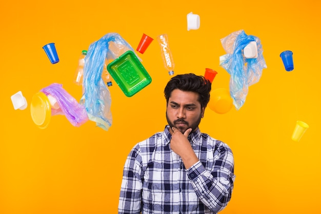 Plastic recycling problem and environmental disaster concept - worried indian man looking aside on yellow background. he is thinking about ecology