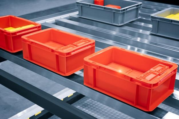 Пластиковая красная коробка на роликовой линии для передачи производственной части в prodine lin на заводе, производстве, концепции транспортировки