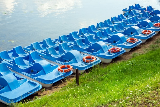 Plastic rental pedal boats parked on the lake shore on a sunny day.