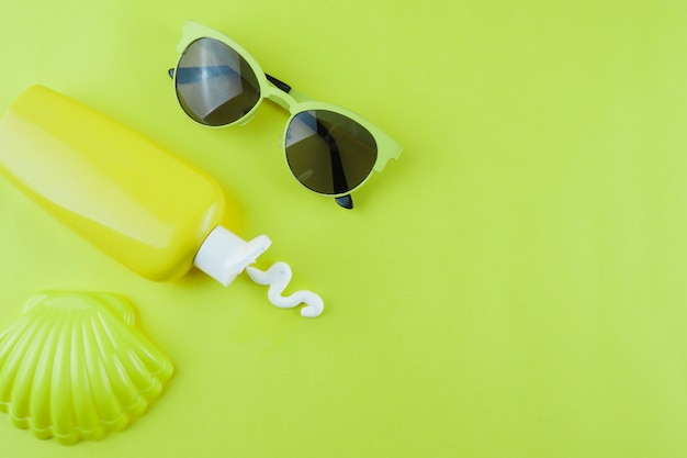 Plastic scallop; sunscreen lotion and sunglasses on green background
