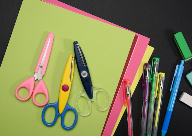 Plastic scissors and colored paper on a black background, back to school backdrop