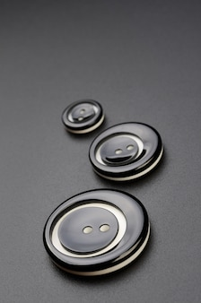 Plastic sewing buttons are arranged in a row on the black surface.