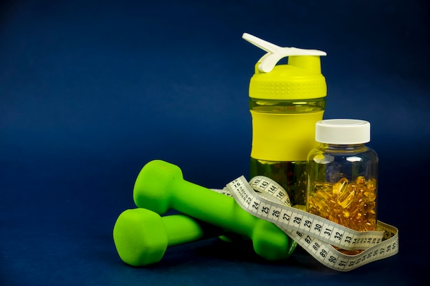 Plastic shaker, green dumbbells and a can of omega 3