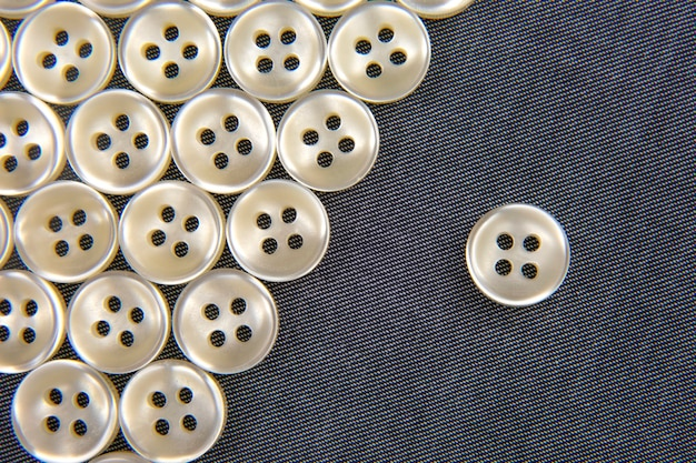 Plastic shiny buttons for clothes on a fabric background. fashion and clothing. factory industry.
