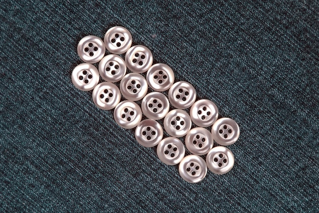 生地の背景に服のプラスチックの光沢のあるボタン。ファッションと服。工場産業。