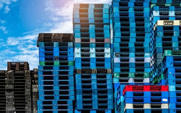 판매 및 임대 사업을위한 플라스틱 운송 팔레트. 공장 창고에 쌓인 산업 플라스틱 팔레트. 화물 및 운송 사업 개념입니다. 플라스틱 팔레트의 더미.