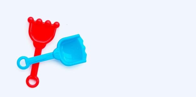 白い表面の砂のためのプラスチック製のシャベルのおもちゃ