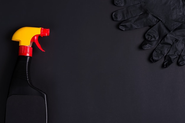 Plastic spray bottles and rubber gloves on a black background. cleaning concept