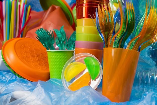 周りのプラスチックのもの。ラップに集められたさまざまなサイズとテクスチャの使い捨てプラスチックカトラリー
