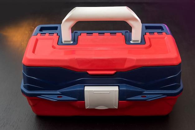 ツールロック付きのプラスチック製のスーツケースボックスは、暗い隔離された背景に隔離されています。業界 Premium写真