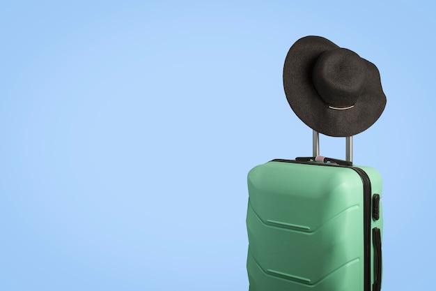 ホイールのプラスチックスーツケースと青色の背景のハンドルにつばの広い帽子。旅行の概念、休暇旅行、親戚への訪問