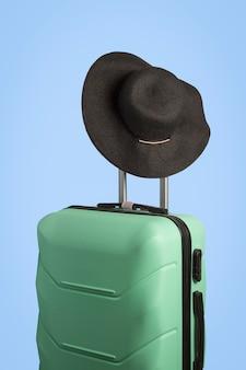 車輪付きのプラスチックスーツケースと、青い壁のハンドルにつばが広い帽子。旅行の概念、休暇旅行、親戚への訪問