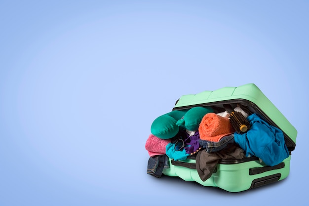 Plastic suitcase with wheels, overflowing things on a blue background. travel concept, vacation trip, visit to relatives