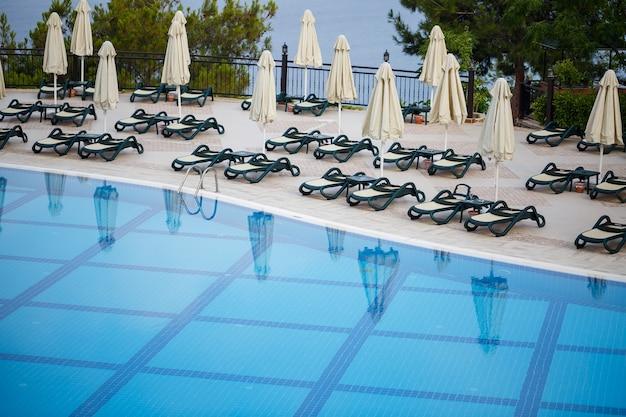 Пластиковые шезлонги и зонтики для защиты от солнца расставлены на плитке у бассейна в зоне отдыха.