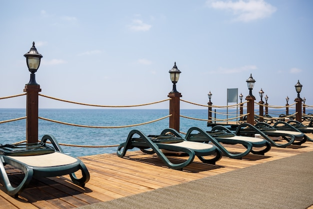 Plastic sun loungers stand in a row on the pier on the beach by the sea