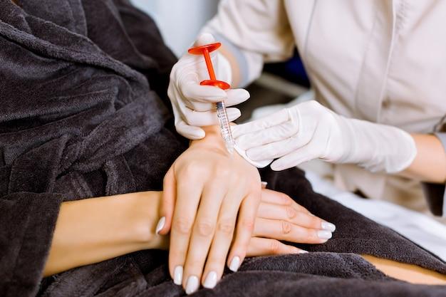 Врач пластический хирург делает укол красоты в руки молодой женщины.