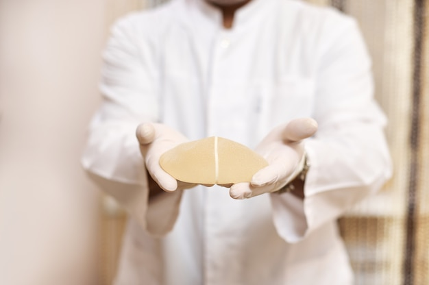Plastic surgeon holds breast implant and shows it to the camera standing on the surface of wall in his cabinet