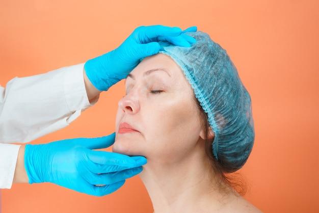의료 장갑에 성형 외과 의사는 아름다운 중년 여성, 성형 수술 개념의 얼굴을 검사합니다