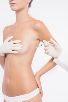 Plastic surgeon injecting in woman breast