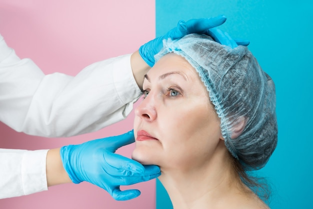 Пластический хирург готовит пожилую женщину к пластической хирургии.