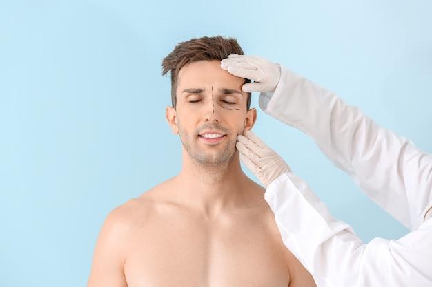 Пластический хирург трогает лицо молодого человека на цветной поверхности